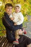 Mum with the child. On a bench, autumn royalty free stock photo