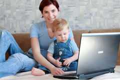 Mum with the child. Young mum with the small beautiful boy together sit near laptop Royalty Free Stock Image