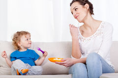 Mum and child eating meal together Stock Photo