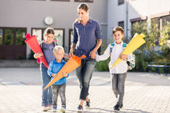Mum and children with paper funnels for candy after first day at Royalty Free Stock Images