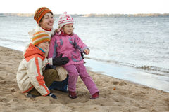 Mum with children sit on river bank stock photography
