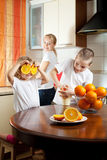 Mum with children squeezed orange juice Royalty Free Stock Images