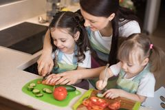 Mum chopping vegetables with kids daughters in a family home kitchen. Royalty Free Stock Images