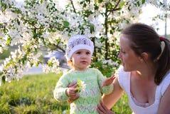 Mum com a criança nas flores foto de stock royalty free