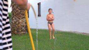Mum com o filho que faz correria com a mangueira exterior vídeos de arquivo