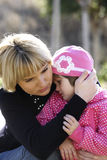 Mum comforting her baby girl. A picture of a mum comforting and hugging her baby girl in the park stock images