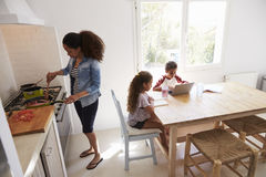 Mum cooking while kids work at kitchen table, elevated view Stock Photos