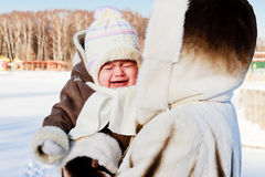 Mum with crying baby outside in cold. Mother trying to calm down crying baby in winter Royalty Free Stock Images