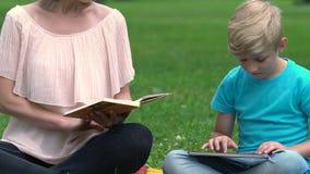 Mum czytelnicza książka podczas gdy syn pisać na maszynie na pastylce w parku, zabawie i czasie wolnym, wpólnie zbiory