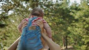 Mum da beleza e sua criança que jogam no parque junto vídeos de arquivo