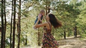 Mum da beleza e sua criança que jogam no parque junto video estoque