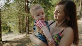 Mum da beleza e sua criança que jogam no parque junto filme