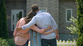Mum dad and girl hugging, looking at new house, togetherness and care concept. Stock footage stock video footage