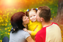 Mum and dad kissing cheeks of daughter Stock Photo