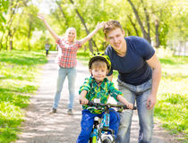 Mum and dad taught his son to ride a bicycle in the park Stock Photos