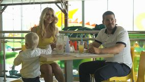 Mum dad and two year old son eating food. Happy family - mum dad and two year old son eating food in children`s cafe stock footage