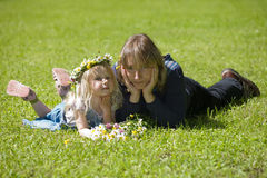 Mum and daughter. Mum with a daughter lie on a grass and hold hands about the face royalty free stock photos