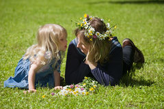 Mum and daughter. Lie on a grass, the daughter reached to kiss mum stock image