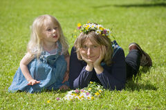 Mum and daughter. Mum with a daughter lie on a green grass with a bunch of flowers stock images
