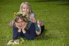 Mum and daughter. Portrait of a mother lying on the lawn with her daughter sitting on her back, in the outdoors stock images