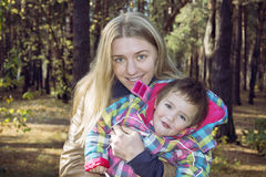 Mum with a daughter in autumn forest. Stock Photography