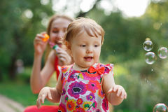 Mum with daughter blowing soap bubbles in park Royalty Free Stock Images