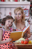 Mum with a daughter and a cookbook Stock Photography