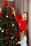 Mum with daughter decorate tree Royalty Free Stock Photos