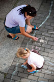 Mum and daughter drawing with chalk. Overhead view of mother and preschool daughter drawing on pavement or sidewalk with colorful chalk Stock Photos