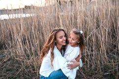 Mum and daughter having fun together outdoors. Smiling mother embraces her pretty little daughter. They walking outdoors royalty free stock images