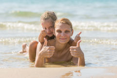 Mum with a daughter on his back lying on the beach and show. Girl and woman show thumbs up. Mother and her sitting on the back of a four-year girl lying in the Royalty Free Stock Images