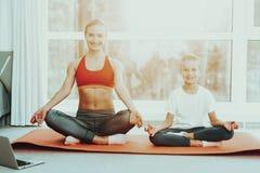 Mum And Daughter Lotus Pose Sitting On Carpet. stock image