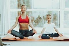 Mum And Daughter Lotus Pose Sitting On Carpet. stock photos