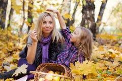 Mum and the daughter play autumn park Stock Photos