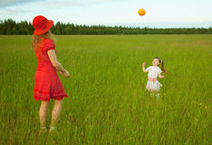 Mum and daughter play with a ball. In the field Stock Photo