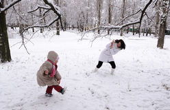 Mum and the daughter play snowballs Stock Image