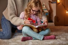 Mum and daughter reading fairy tale in children room stock images