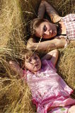 Mum and a daughter relations. Two girls lie on hay royalty free stock photography