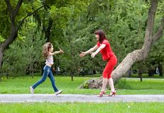 Mum and the daughter run towards each other stock images