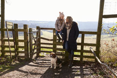 Mum and daughter by rural gate with dog look at each other Stock Image