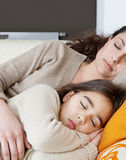 Mum and daughter sleeping on couch Stock Image
