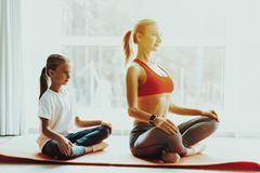Mum And Daughter Yoga Training. Lotus Position. stock images