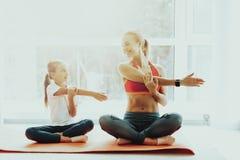 Mum And Daughter Yoga Training. Lotus Position. stock photos