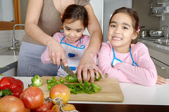 Mum and Daughters Chopping Veggies. Mother and twin daughters learning to chop vegetables together in the kitchen, using a chopping board and surrounded by fruit Royalty Free Stock Photo