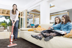 Mum and Daughters Cleaning Living. Young mum using a vacuum cleaner while her two twin daughters look at a book in the living room Royalty Free Stock Photo