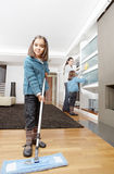 Mum and Daughters Cleaning Living. Mother and daughters cleaning the house together, smiling Royalty Free Stock Images