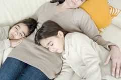 Mum and daughters sleeping on couch Stock Image