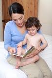 Mum die aan zieke baby leest royalty-vrije stock afbeeldingen