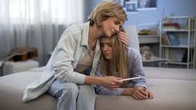 Mum die verstoorde dochter, tienerzwangerschap omhelzen, die test, steun en zorg houden stock foto's