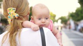 Mum dragende baby en het lopen in stadsstraat stock video